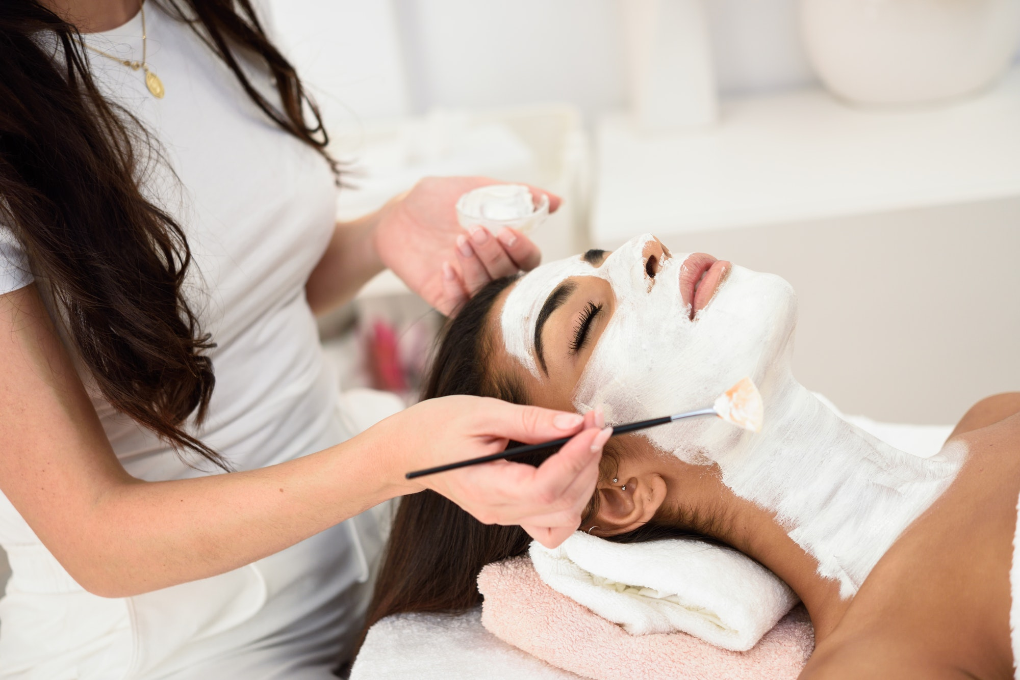 Aesthetics applying a mask to the face of a beautiful woman