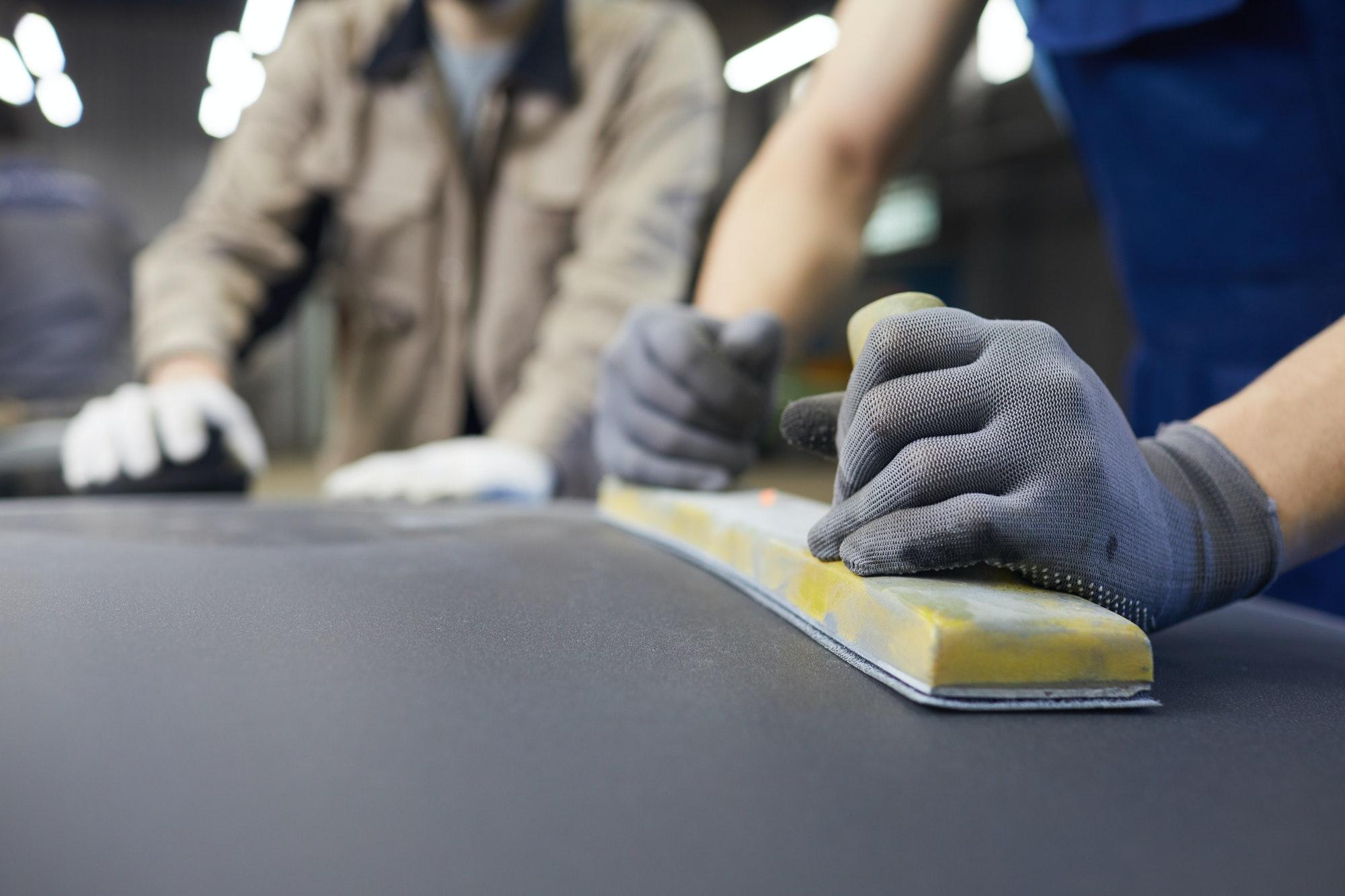 Unrecognizable Men Grinding Car Body Surface