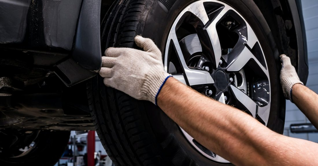 Close up of mechanic removes a wheel from car